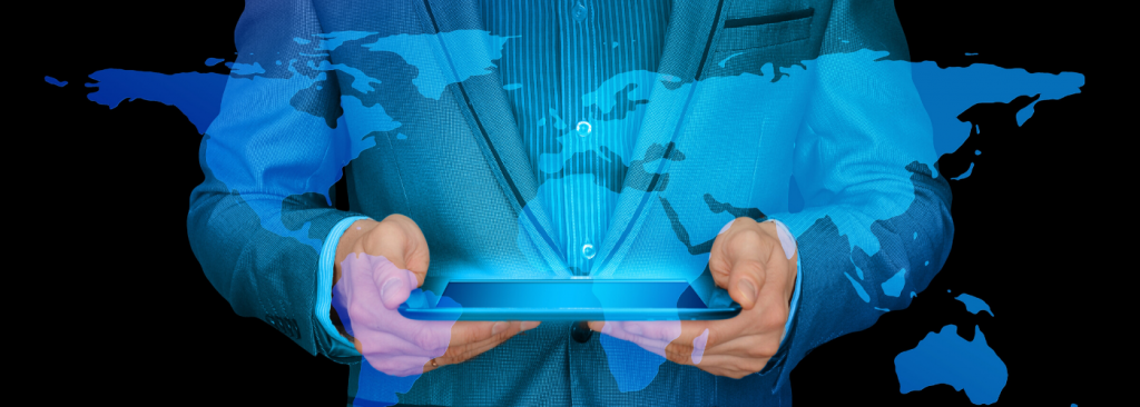 A man holding an iPad that is projecting an image of the world