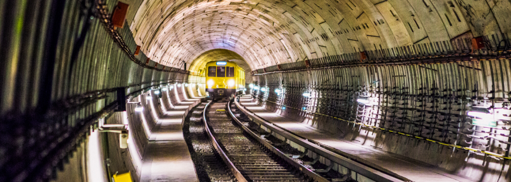 A picture of a yellow underground train in a tunnel